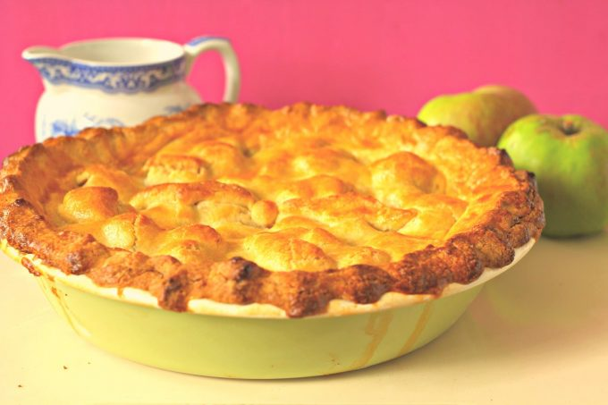apple pie with apples and cream near by