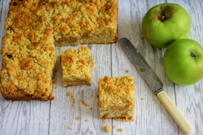 Apple Crumble Cake cut into squares with some cooking apples by the side