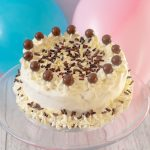 Ice cream birthday cake covered in cream swirls, maltesers and chocolate curls on a glass cake stand with two balloons behind.