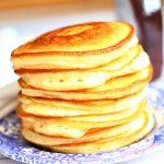 stacked pancakes on a blue and white plate with a jar of maple syrup in the background.
