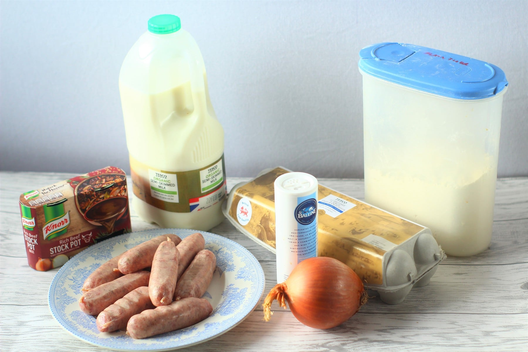 sausages on a plate, onion, salt, stock pots, eggs, flour, milk
