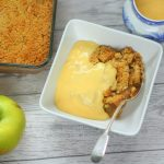 apple crumble with custard in a bowl with bramley apples and a jug of custard nearby.