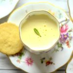 lemon posset in a teacup with a shortbread biscuit