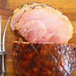 sliced gammon on a wooden chopping board