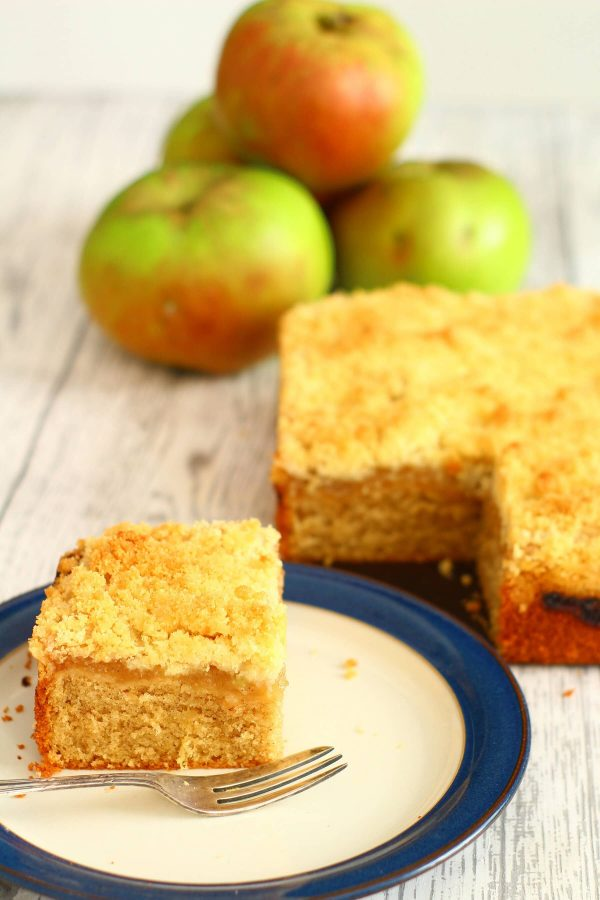 slice of apple crumble cake on a plate with the cake and a pile of apples next to it