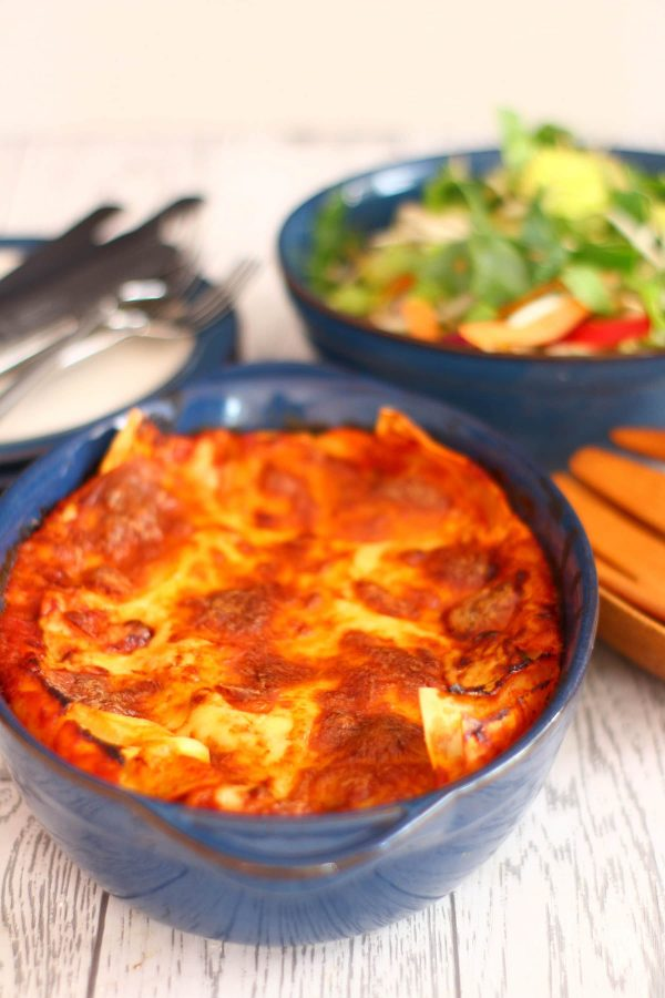 easy vegetable lasagne with plates and a bowl of salad in the background