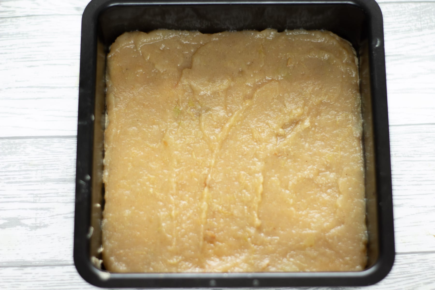 stewed apples spread on a layer of sponge in a cake tin