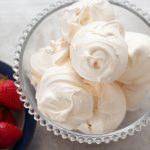 glass bowl filled with meringues, a bowl of strawberries next to it.