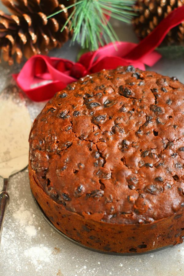 christmas cake with pine cones and ribbon in the background
