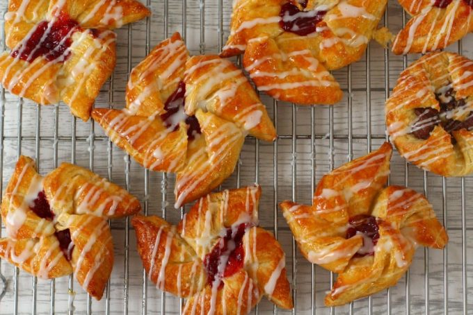danish pastry shapes on a wire rack drizzled with icing sugar
