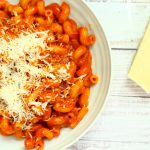 tomato pasta in a bowl with parmesan cheese