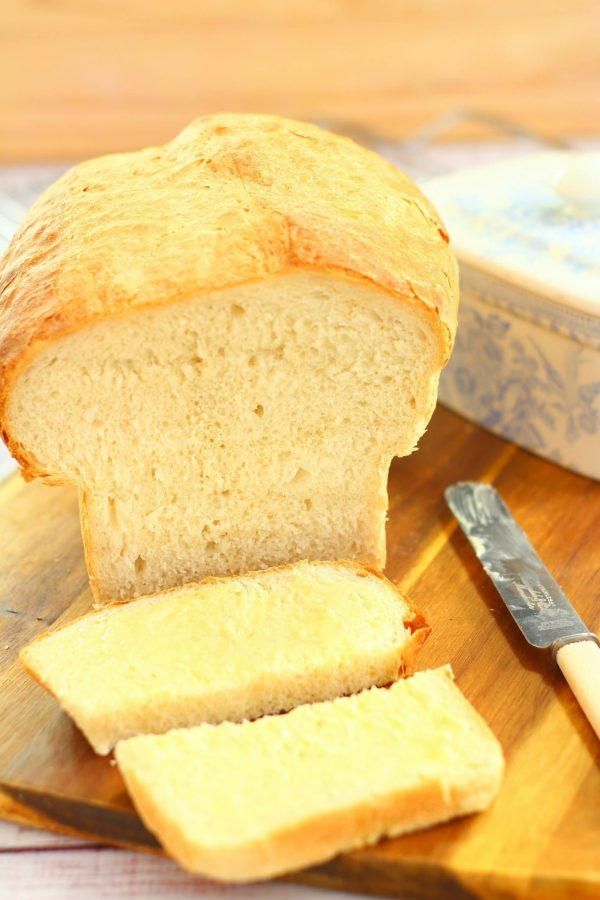 easy white bread on a wooden board with a butter knife and butter