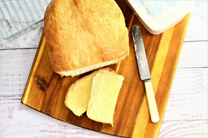 white homemade bread sliced and spread with butter