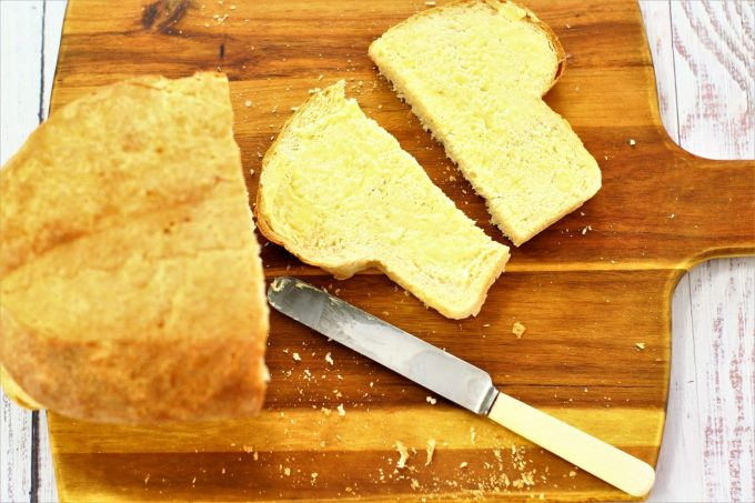 sliced white loaf spread with butter on a wooden board with a knife and butter