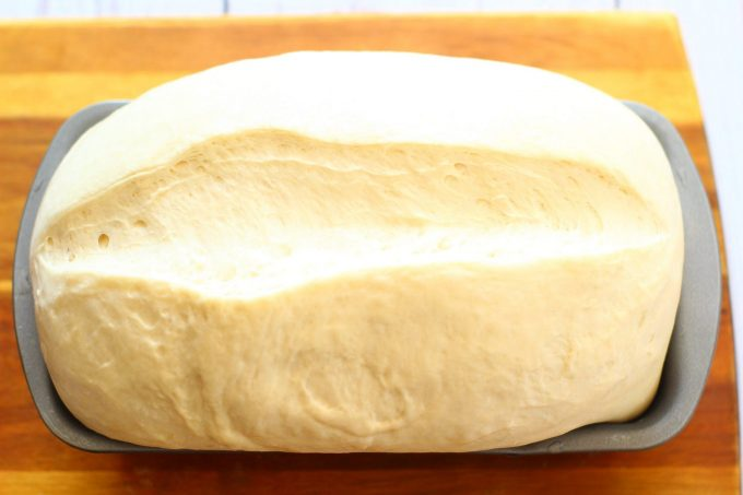 bread dough cut down the middle in a loaf tin