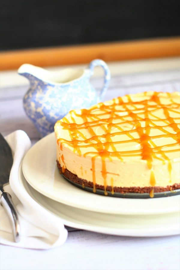 no bake caramel cheesecake on a serving dish drizzled with toffee sauce with a blue cream jug and a serving knife nearby
