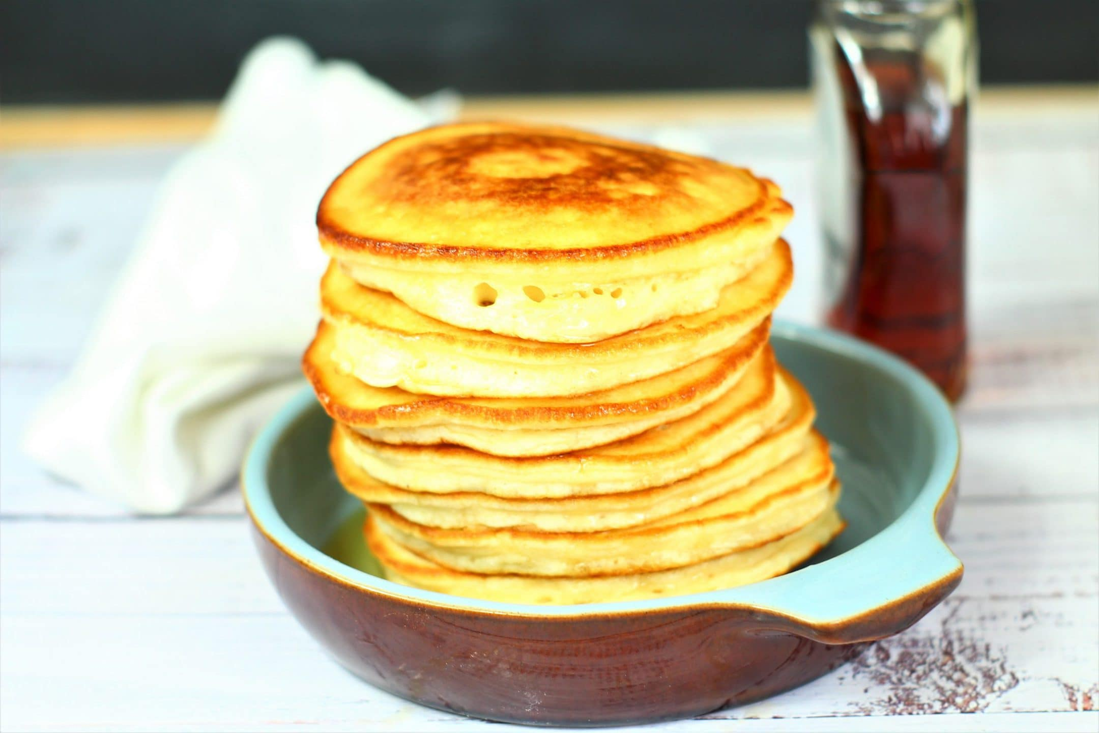 pancakes piled high in a dish with a jar of maple syrup in the background.