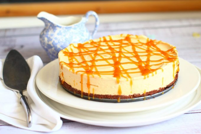 caramel cheesecake drizzled with toffee sauce on a serving plate with a blue jug nearby and a serving slice next to it on a napkin