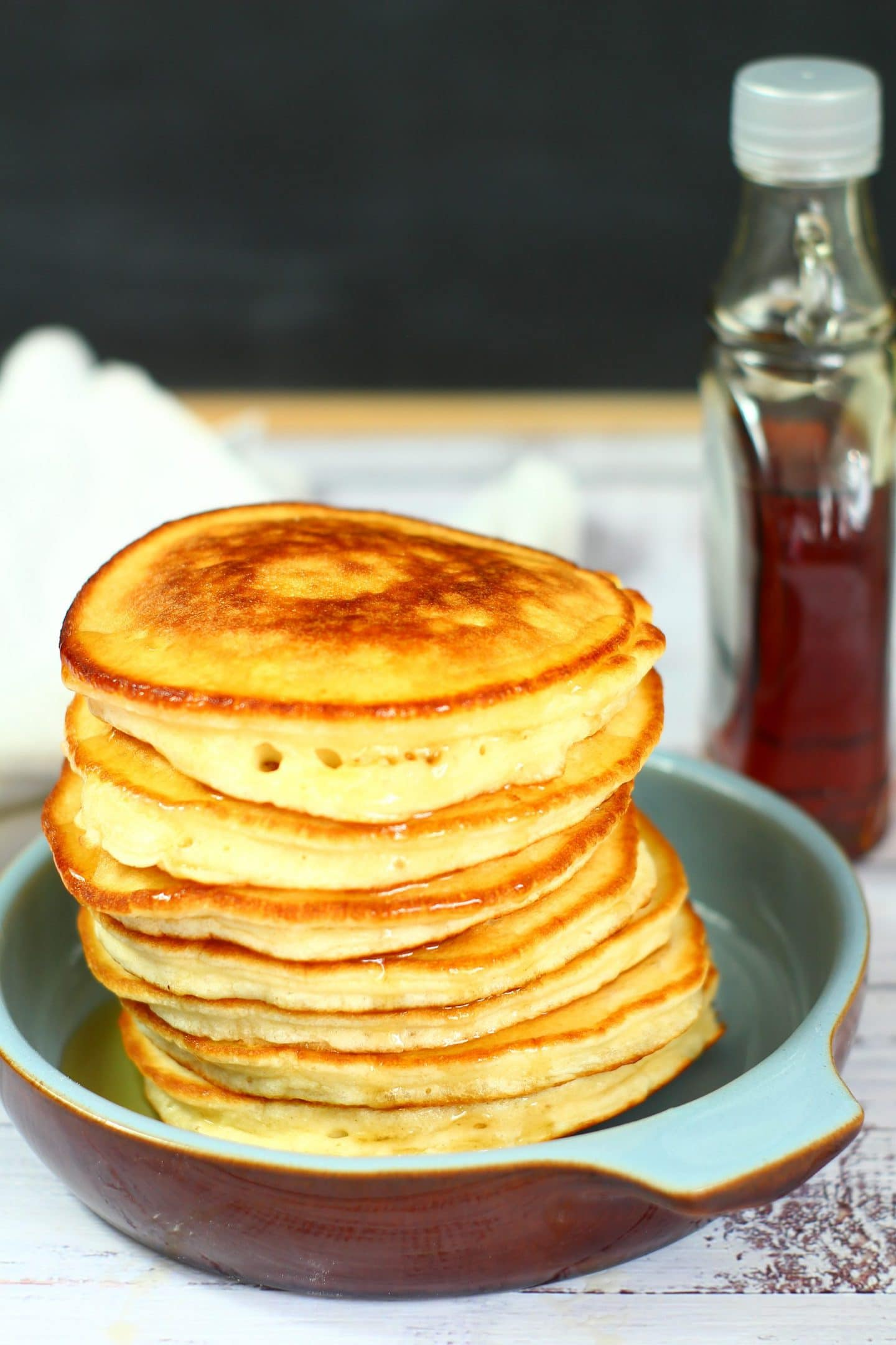 stacked pancakes in a dish with maple syrup in the background.