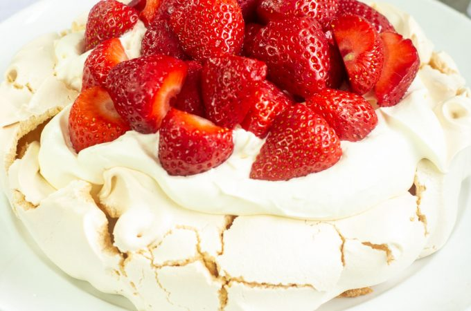 pavlova topped with softly whipped cream and strawberries