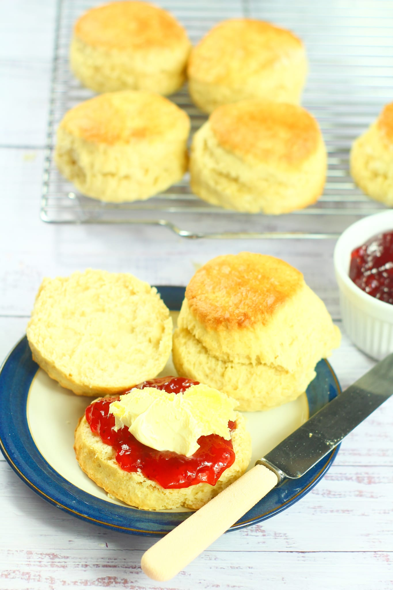 split scone with jam and cream on a small plate with another scone and more scones in the background with a pot of jam on the right
